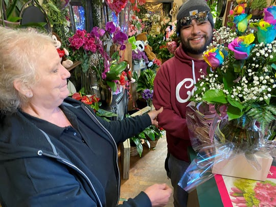 Peter Perkens floral designer Betty Land hands a tie-dyed bouquet to a Valentine's Day customer Thursday in Visalia.