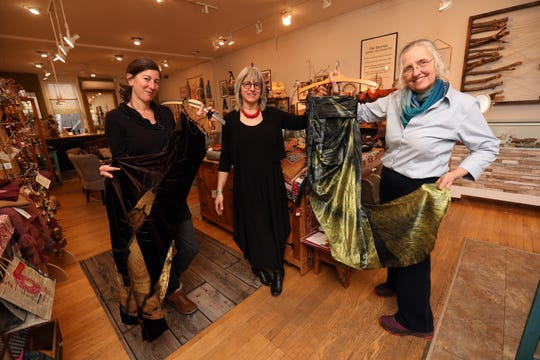 Lamont-Doherty Earth Observatory scientists Nicole Davi, left, and Robin Bell, right, with their climate-themed fashion, and Maria Luisa Whittingham, owner of Maria Luisa Boutique, at the shop in Nyack, Feb. 13, 2020. The climate scientists had their work printed on fabric and incorporated it into fashion. Whittingham helped Bell with her flowing skirt.