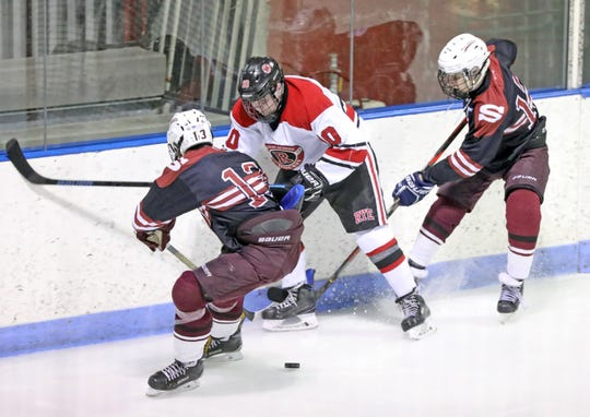 Scarsdale's Jason Koch (13) and Josh Bock (12) try to steal the puck from Rye's Carter Barford (10) during ice hockey game at Playland in Rye Feb. 12, 2020. Scarsdale defeats Rye 7-4.