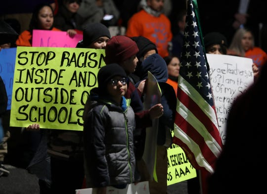 Signs decrying racism are held by attendees during a rally Wednesday in support of Academia Antonia Alonso Charter School and Delaware's Latino community after board members at neighboring Odyssey Charter School made racially insensitive comments.