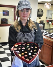 Brooke Willis displays a 27-piece box of specialty chocolates in a Valentine's box at her downtown business, B Cocoa Artisan Chocolate.