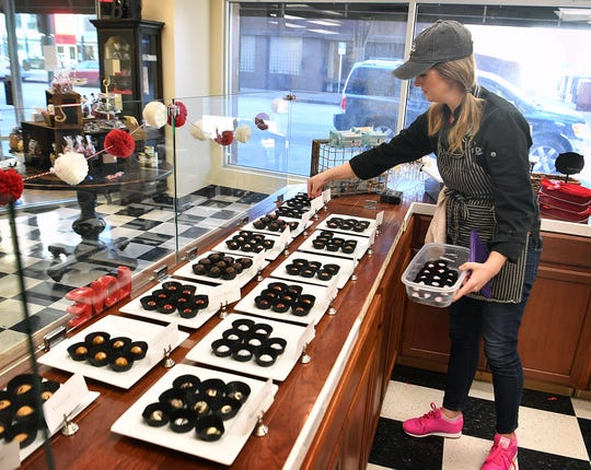 In this file photo from February 2020, Brooke Willis, owner of B Cocoa Artisan Chocolate in downtown Wichita Falls, restocks a selection of her specialty chocolate items. Retail spending, along with income increases, has helped the Wichita Falls economy more than sustain a lack of population growth.