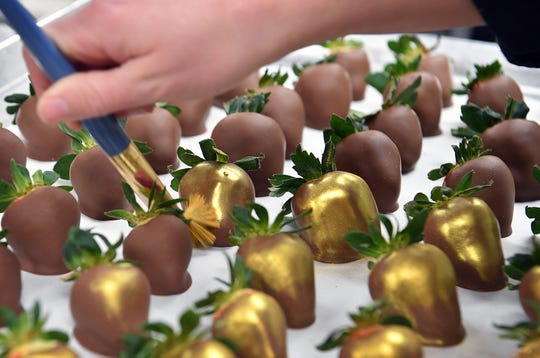 Chocolate-dipped strawberries get an application of gold 'luster dust' at B Cocoa Artisan Chocolate for a Valentine's Day special touch.