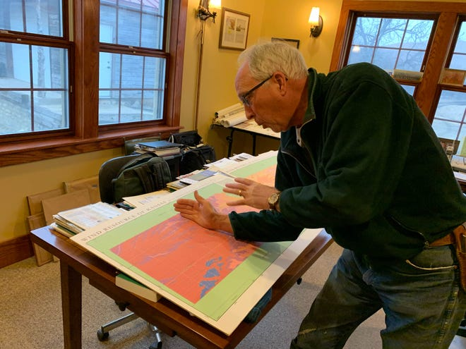 Pete Ferrell, 67, on his family's fourth-generation cattle ranch near Beaumont, Kansas. He helped start the Elk River Wind Farm. Here he is showing a map of the wind resource in Kansas.