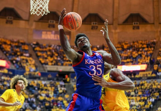 Kansas Jayhawks center Udoka Azubuike (35) receives a pass in the lane while defended by West Virginia Mountaineers forward Oscar Tshiebwe (34) during the first half at WVU Coliseum.