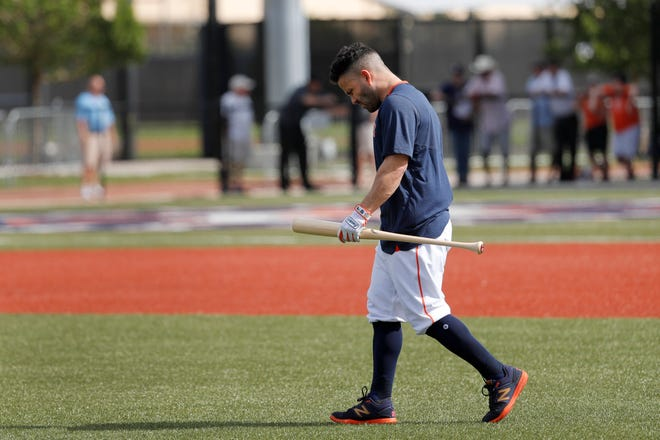 Astros' Jose Altuve carries a bat as he heads out to hit.