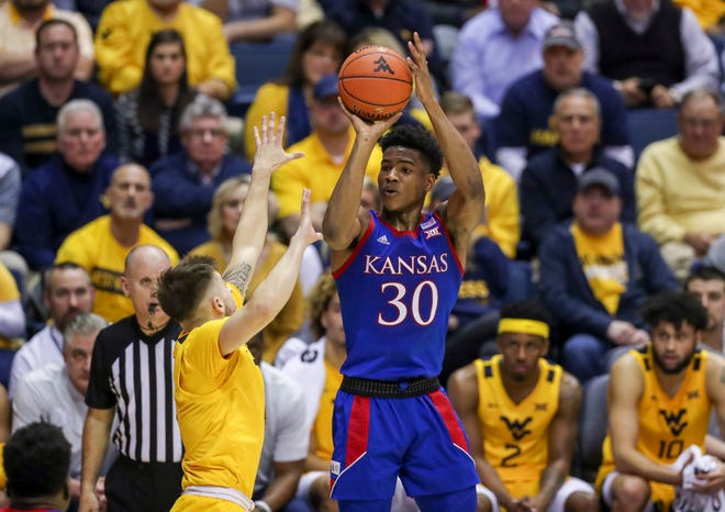 Kansas guard Ochai Agbaji shoots a three pointer over West Virginia guard Jordan McCabe during the first half at WVU Coliseum.