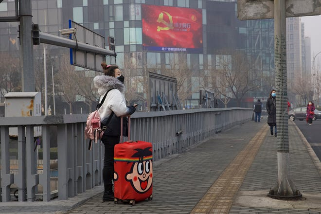 A traveler stands on a nearly empty street in Beijing, China, on Thursday, Feb. 13, 2020.