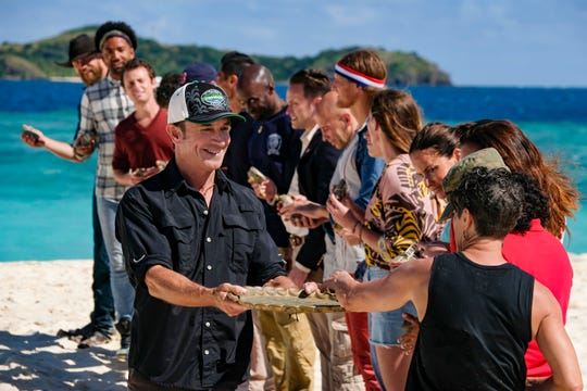 """Survivor"" host Jeff Probst, left front, hands 20 'Winners at War' competitors information that will reveal which team they will be on during Wednesday's premiere of the first all-champions edition."