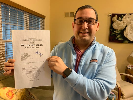 Jason Krynicki holds up a the legislature's resolution on Obesity Care Week in New Jersey, signed by Gov. Phil Murphy.