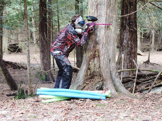A player hides behind a tree at Northwest Paintball Park. The park's owners announced it would close this month after 20 years in business.