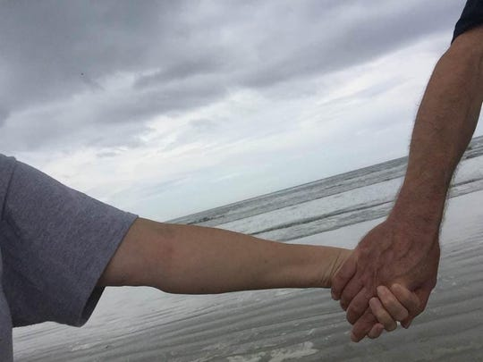 """Britt Kennerly and her husband, Doug, take a walk on Cocoa Beach. She says of their years together: """"Even when it's nastyto its core, this """"us"""" stuff isbeautiful."""""""