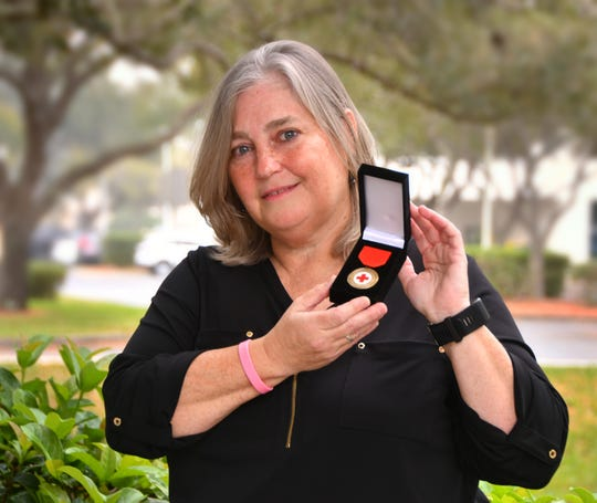 Kate Dilulio was jogging on River Road last August when her running buddy, who she only knew to run with occasionally, had a heart attack. She performed CPR on him, saving his life. On Friday morning, Valentine's Day, she received the Life Saving award from the Space Coast Chapter of the Red Cross.