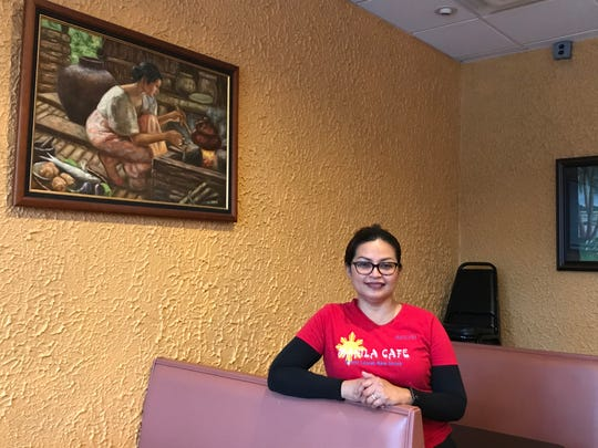 Arlyn Baker, owner of Manila Cafe in Mount Laurel, stands next to a painting in her restaurant. Homesick for her native country, she opened the Filipino cafe.