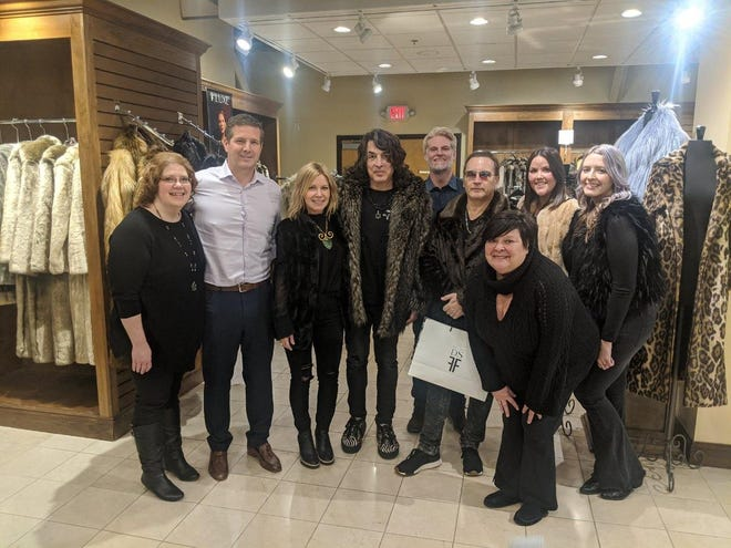 Employees at Donna Salyers' Fabulous-Furs pose with KISS stars Paul Stanley and Eric Singer.