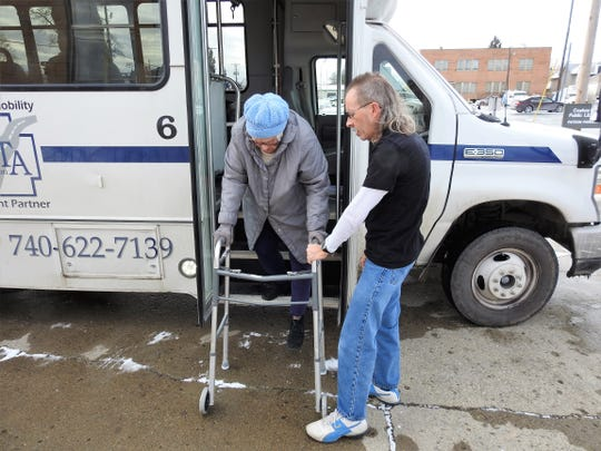 Donna Smith is helped off of the Coshocton County Coordinated Transportation Agency's new public shuttle by driver John Clark. Smith did some shopping at Walmart and dropped off some books at the Coshocton Public Library on Friday, which was a free ride day.