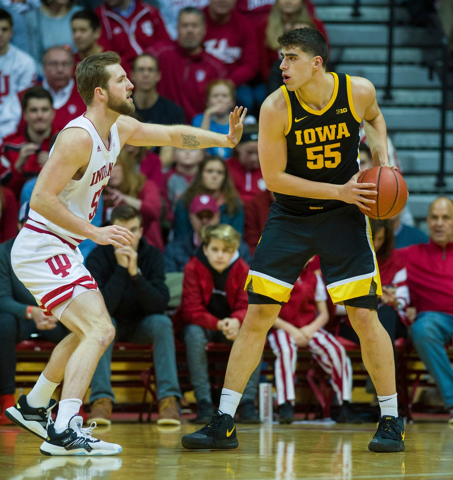 Iowa center Luka Garza (55) is defended by Indiana forward Joey Brunk (50) during the first half of an NCAA college basketball game, Thursday, Feb. 13, 2020, in Bloomington, Ind. (AP Photo/Doug McSchooler)