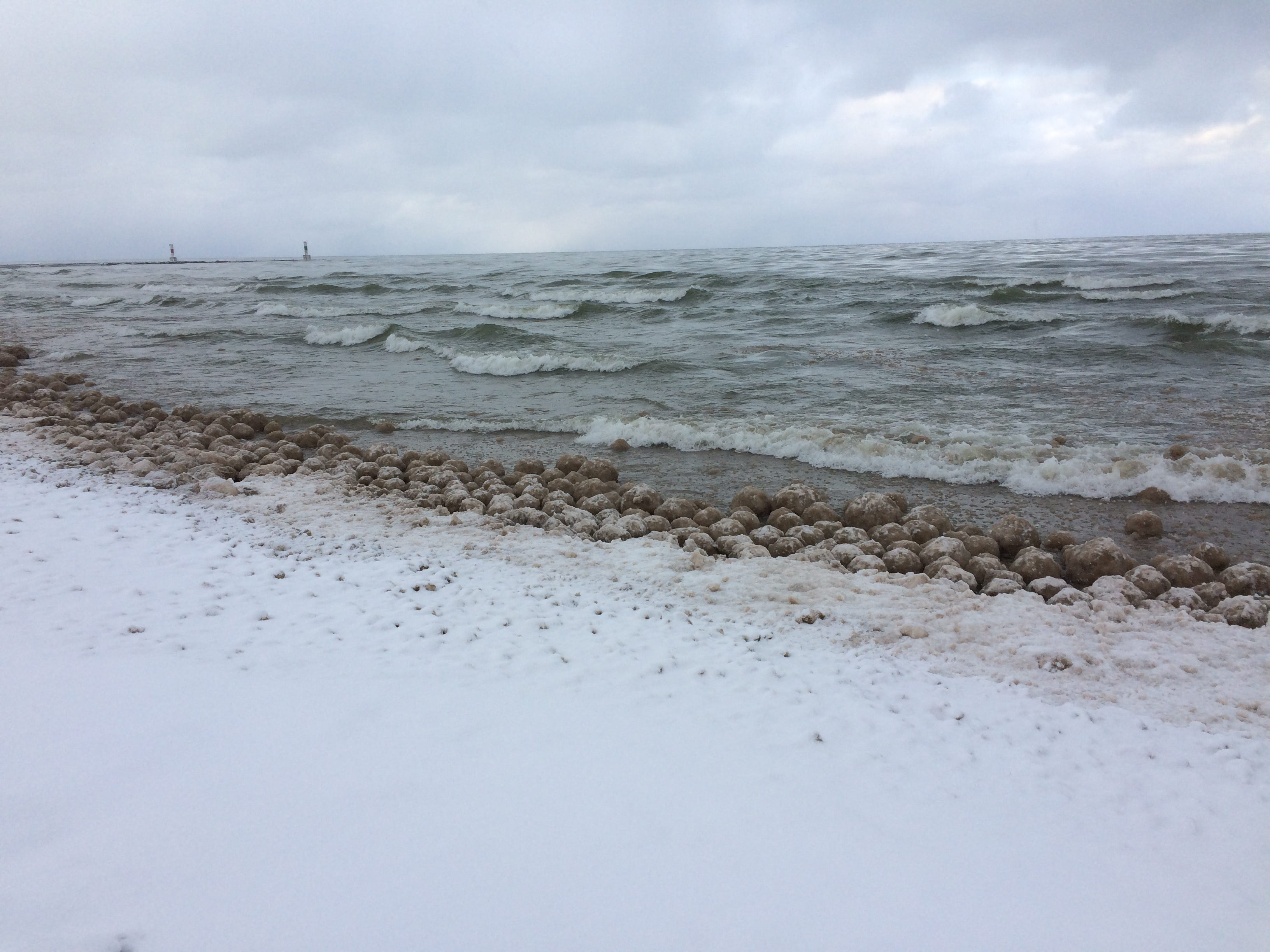 Thousands of rare ice balls appear on Lake Michigan beach, some as big as yoga balls