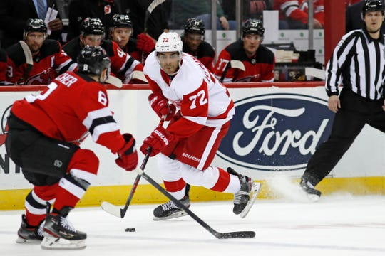 Detroit Red Wings left wing Andreas Athanasiou looks for an opening with New Jersey Devils defenseman Will Butcher defending during the first period Feb. 13, 2020, in Newark, N.J.