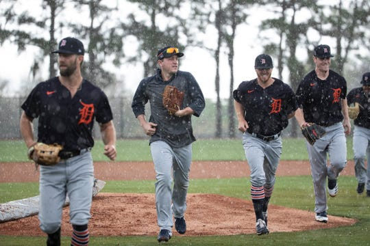 Pitchers, including, Daniel Norris, Jordan Zimmermann, and Joey Wentz, run off the field due to rain during spring training at TigerTown in Lakeland, Fla., Friday, Feb. 14, 2020.