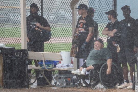 Detroit Tigers players and fans stay under a shed as it rains during spring training at TigerTown in Lakeland, Fla., Friday, Feb. 14, 2020.