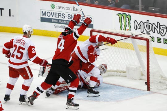 New Jersey Devils' Miles Wood celebrates as a shot by Wayne Simmonds (not shown) goes into the net behind Detroit Red Wings goaltender Jonathan Bernier as defenseman Mike Green watches during the third period Thursday, Feb. 13, 2020, in Newark, N.J.