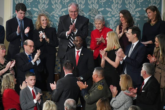 "In this Feb. 4, 2020, photo, Tony Rankins, center in red tie, receives a standing ovation during the State of the Union address to a joint session of Congress on Capitol Hill in Washington. Rankins, a formerly homeless, drug-addicted Army vet, got the standing ovation after President Donald Trump described how he turned his life around thanks to a construction job at a company using the administration's ""Opportunity Zone"" tax breaks."