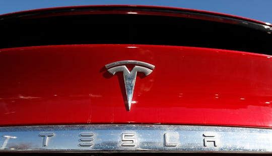 FILE - In this Feb. 2, 2020 file photograph, the company logo sits on an unsold 2020 Model X at a Tesla dealership in Littleton, Colo.