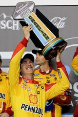 Joey Logano holds up his trophy after winning the first of the two NASCAR Daytona 500 qualifying auto races at Daytona International Speedway.
