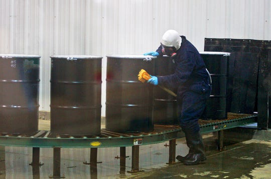 In this Monday, Dec. 9, 2013, file photo, a worker decontaminates steel drums containing yellowcake uranium to ensure safe shipment at UR Energy's Lost Creek uranium production facility in Sweetwater County, Wyo. The Trump administration is asking Congress for $1.5 billion over 10 years to build up a U.S. uranium stockpile, saying it wants to break an over-reliance on foreign uranium.