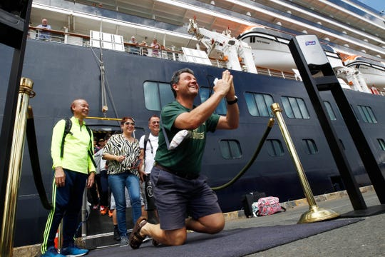 Passengers react after they disembarked from the MS Westerdam, back, at the port of Sihanoukville, Cambodia, Friday, Feb. 14, 2020. Hundreds of cruise ship passengers long stranded at sea by virus fears cheered as they finally disembarked Friday and were welcomed to Cambodia.