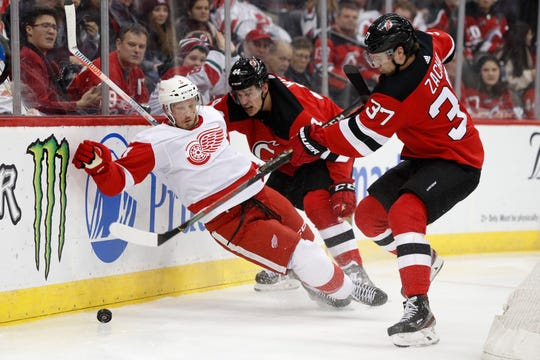 Detroit Red Wings defenseman Alex Biega (3) slips as New Jersey Devils center Pavel Zacha (37) tries to get control of the puck wiht Devils left wing Miles Wood (44) defending Biega during the second period.