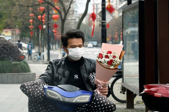 A man wearing a face mask carries a Valentine's Day bouquet as he rides a scooter in Hangzhou in eastern China's Zhejiang Province, Friday.