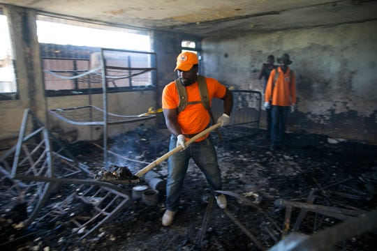 A civil protection worker shovels charred debris from inside the Orphanage of the Church of Bible Understanding where a fire broke out the previous night.