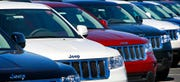"This Nov. 30, 2010, file photo, shows a row of Jeep Grand Cherokees on a dealership lot. Fiat Chrysler's use of $1,500 ""bonus cash coupons"" to incentivize dealers to purchase overstocked vehicles from the manufacturer is seen by some as an unfair advantage for larger dealerships with ""broader spending resources allotted for vehicle acquisitions."""