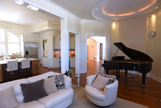 The great room with piano alcove near the kitchen of the $1.39 million French provincial.