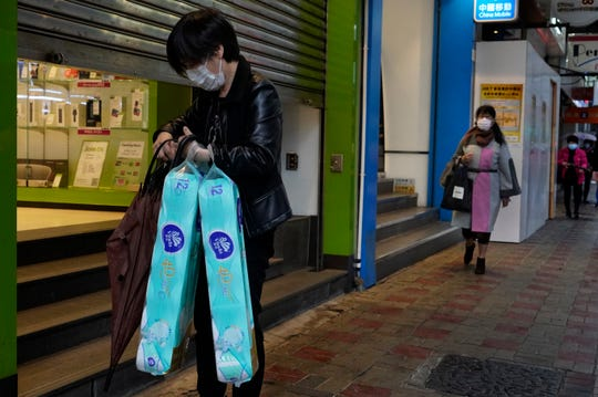A woman wearing a protective face mask as she carries a supply of toilet paper on a street in Hong Kong, Friday, Feb. 14, 2020. China has reported another sharp rise in the number of people infected with a new virus, as the death toll neared 1,400