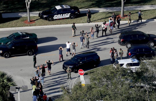 Students hold their hands in the air as they are evacuated by police from Marjory Stoneman Douglas High School in Parkland, Fla., after a shooter opened fire on the campus on Feb. 14, 2018.