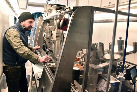 Andy Savina, operations manager for Harbor Hill Mobile Bottling, runs the machinery at Aurora Cellars near Lake Leelanau, Mich. Wednesday, Feb. 12, 2020.