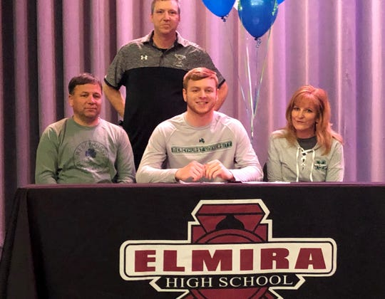 Elmira senior Nate Latshaw signs to play soccer at Mercyhurst University on Feb. 13, 2020. Next to him are his parents, Brian and Lesley Latshaw. In the back is Elmira boys lacrosse coach Jason Stukey.