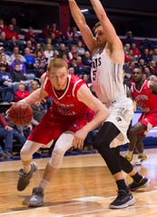 University of Southern Indiana's Justin Carpenter (20) drives the ball against Lindenwood's  Luka Radosevic (5)  as the University of Southern Indiana Screaming Eagles play the Lindenwood University Lions at Screaming Eagles Arena Thursday evening, Feb 13, 2020.
