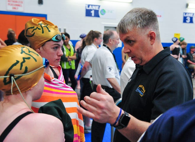 Ed McNamee, who coaches both the CMR and Great Falls High swim teams, talks to a couple of his swimmers on Friday during the state swim meet at the Great Falls High pool.