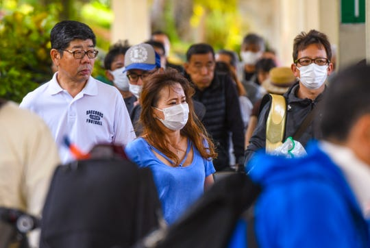 Several passengers can be found wearing face masks after their arrivals on flights at the A. B. Won Pat International Airport in Tamuning on Friday, Feb. 14, 2020.
