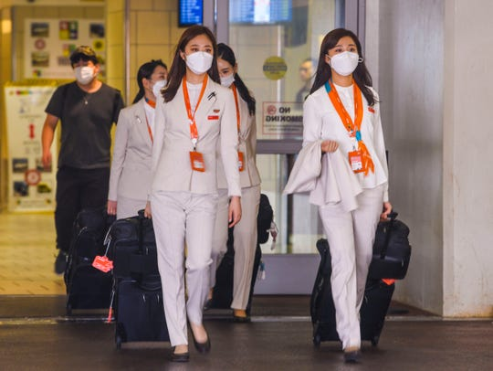 Jeju Air flight attendants can be seen wearing face masks in the arrivals section of the A. B. Won Pat International Airport in Tamuning on Friday, Feb. 14, 2020.