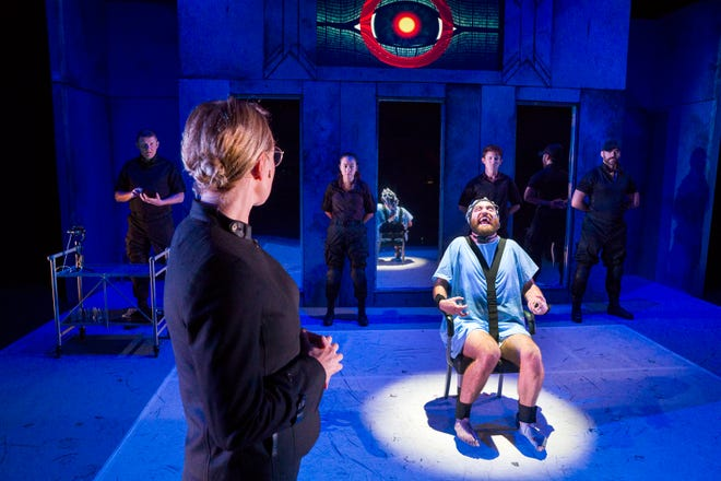 """The imprisoned protagonist Winston (played by Reece Richardson) endures electrical shock under the impassive gaze of the interrogator O'Brien (Hannah Sinclair Robinson, foreground) and four Party members during a scene in """"George Orwell's 1984."""" The stage-adapted play will be presented at 7:30 p.m. Friday, Feb. 21, at the Preston Arts Center."""