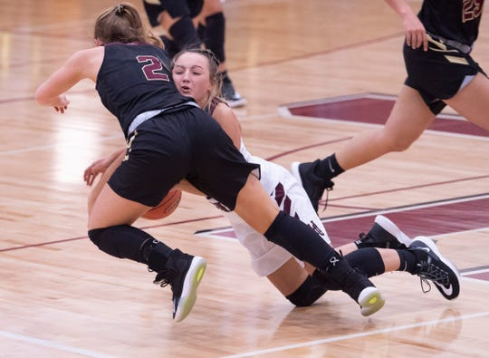 Webster County's Marissa Austin (2) is fouled by Henderson County's Savannah Lacer (4) at Henderson High School Thursday night.at Henderson High School Thursday night.