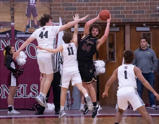 Webster County's Hunter McNaughton (24) pulls down a rebound against Henderson County's Koby Reed (44) and Henderson County's Luke Fulkerson (11) at Henderson High School Thursday night.