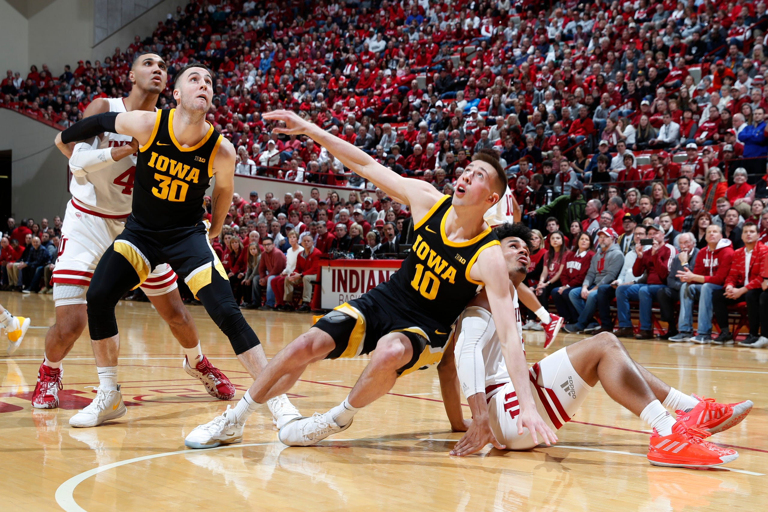 Feb. 13, 2020; Bloomington, Indiana, USA; Indiana Hoosiers forward Justin Smith (3) and Iowa Hawkeyes guard Joe Wieskamp (10) slip on the floor while battling for rebounding position during the first half at Simon Skjodt Assembly Hall.