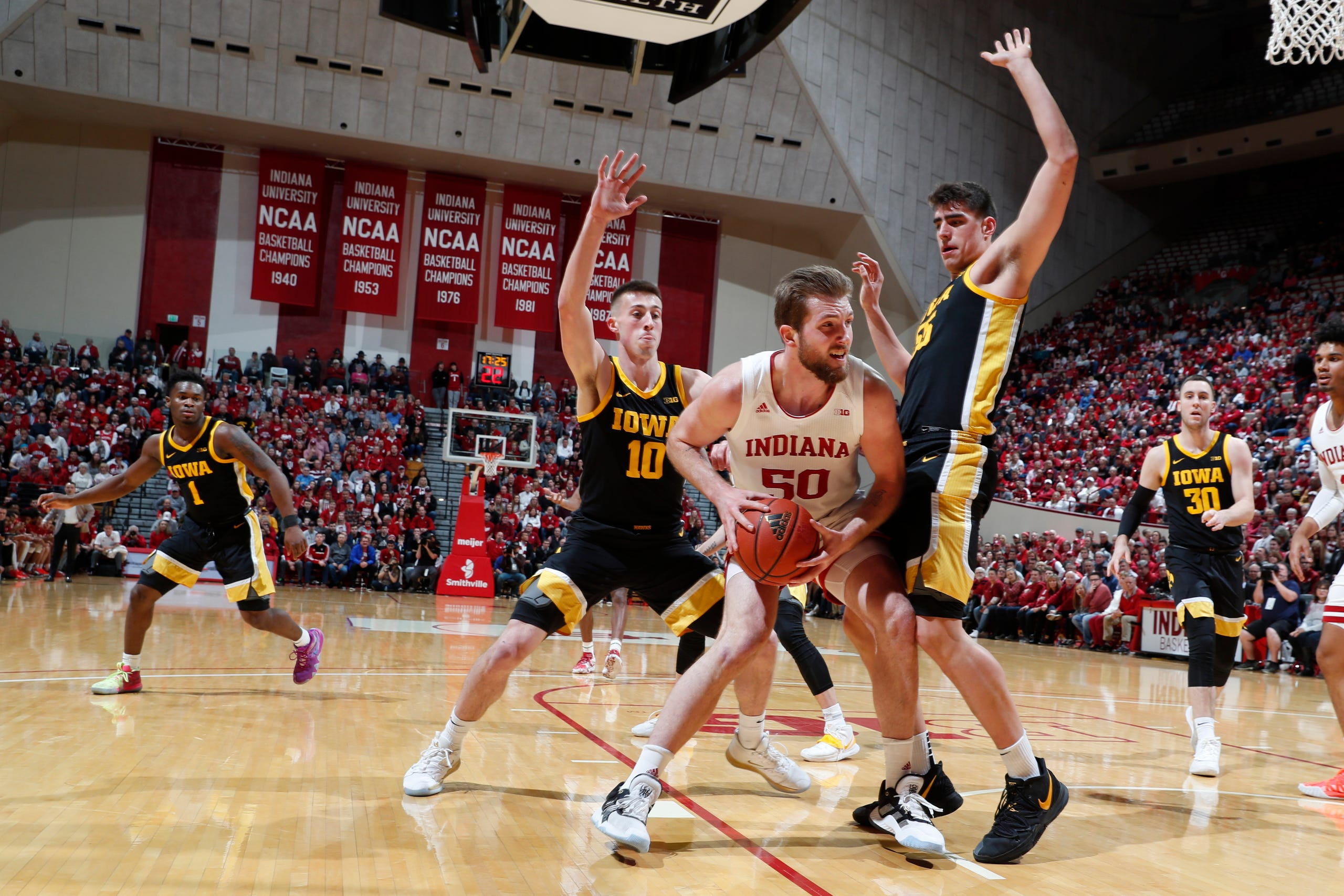 Feb. 13, 2020; Bloomington, Indiana, USA; Indiana Hoosiers forward Joey Brunk (50) is guarded by Iowa Hawkeyes center Luka Garza (55) and guard Joe Wieskamp (10)  during the first half at Simon Skjodt Assembly Hall.