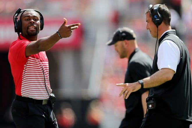 University of Cincinnati assistant coach Mike Mickens, left, is in line to become Notre Dame's new cornerbacks coach.